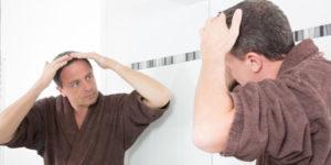 Homme qui regarde l'état de ses cheveux sur le miroir - DHT et perte de cheveux masculine